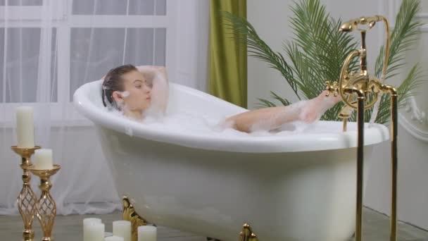 Krásná žena odpočívající v bublinkové koupeli ležící ve vaně. Kosmetická péče, volnočasová aktivita a koncepce zdravotní péče