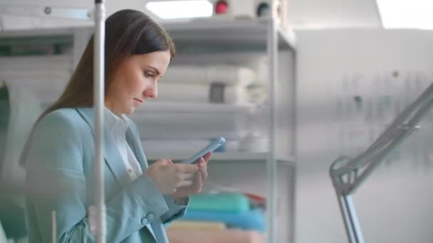 Egy fiatal női divattervező mobiltelefonnal a varróműhelyben üzeneteket ír az ügyfeleknek..