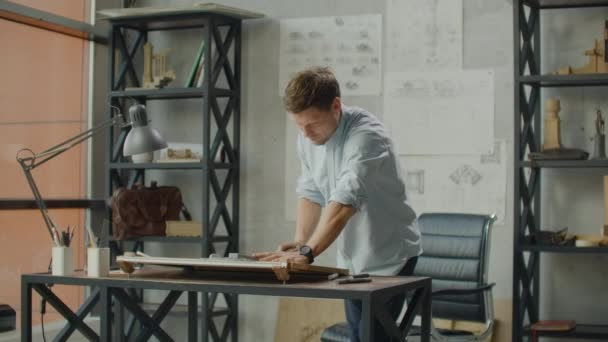 Architects desk: drawings, tape measure, ruler and other drawing tools. Engineer works with drawings in a bright office, close-up. Insturments and office for designer. Male hands draw with a pencil