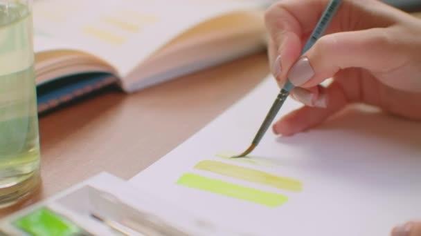 Mladá žena se štětcem a barvami si vybere vhodný odstín pro design loga nebo stěny. Výběr barvy a odstínu pro budoucí design. Žena barvíř v kanceláři s velkými okny čerpá