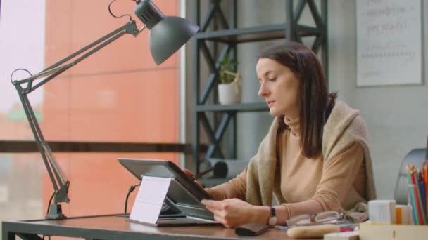 Profesionální designér v kanceláři kreslí stylus na grafickém tabletu, který sedí v kanceláři s obrovskými okny v podkrovním stylu. Moderní kancelář grafika a tvůrce