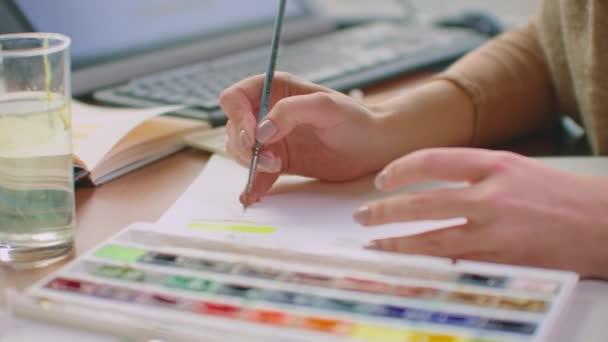 Eine junge Frau wählt mit Pinsel und Farbe einen passenden Farbton für das Logo-Design oder die Wände. Farb- und Farbwahl für zukünftiges Design. eine Koloristin in einem Büro mit großen Fenstern zeichnet