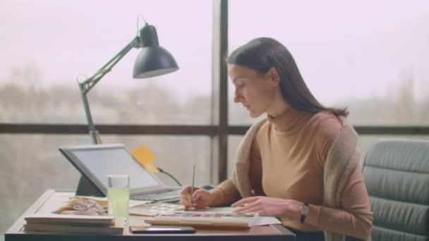 Mladá žena se štětcem a malování barevné párování, vytvořit paletu barev pro barevné párování pro design.
