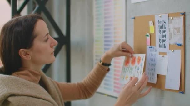 Mladá žena barevná návrhářka sbírá barvy stojící u zdi. Dívám se na stěnu skic a květin. Vybrat správnou barvu
