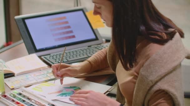 Mladý grafik pracující na moderním stolním počítači při použití grafického tabletu na stole v kanceláři