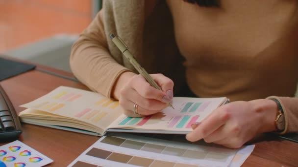 Žena pracující se vzorky barev pro výběr. Koncept interiérového designu a renovace - žena pracující s barevnými vzorky pro výběr.