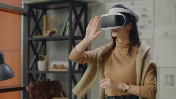 junge Designerin im Büro in Virtual-Reality-Helm mit Händen macht Bewegungen, die die Arbeit der grafischen Oberfläche imitieren