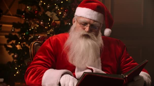 Mikulás szemüveggel és fehér szakállal, olvasás egy piros könyvet a háttérben egy karácsonyfa és egy kandalló.