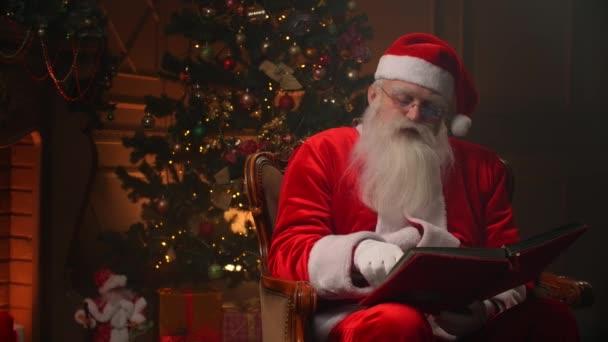 Vidám Mikulás záradék ül a rocker díszített szobában, olvasás egy könyvet piros borító - ünnepi hangulat, karácsonyi szellem koncepció.