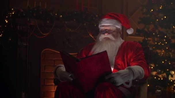 Senior férfi télapó záradék ruházat ül a hangulatos szobában, olvasás egy varázslatos fényes könyv piros borító - karácsonyi szellem, ünnepek és ünnepségek koncepció.