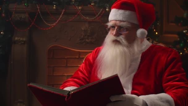 Na Štědrý večer, v útulné atmosféře, Santa Claus čte červenou knihu na pozadí krbu a vánoční stromek s věnci.