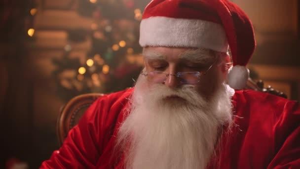 Moderní Santa Claus. Veselý Santa Claus pracuje na notebooku a usmívá se, zatímco sedí u svého křesla s krbem a vánoční strom v pozadí.