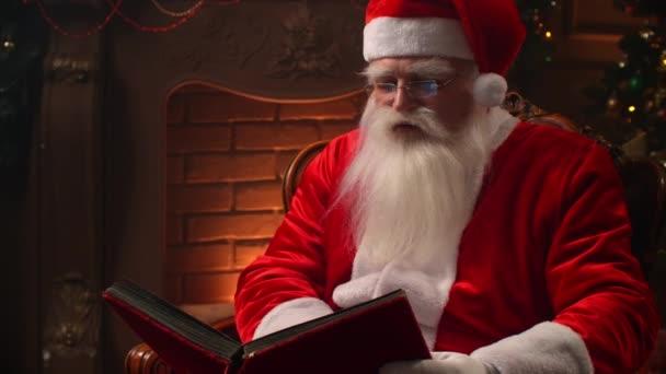 Régi Mikulás szakállas olvasás egy könyvet a háttérben egy karácsonyfa