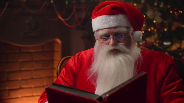 Starší muž s bílým vousem v obleku Santa Clause sedí v křesle na pozadí zdobeného vánočního stromku s věncem čte a listuje stránkami knihy