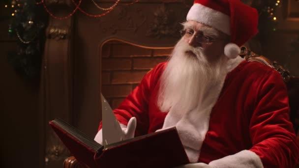 Igazi Mikulás olvas egy könyvet otthon a kandalló
