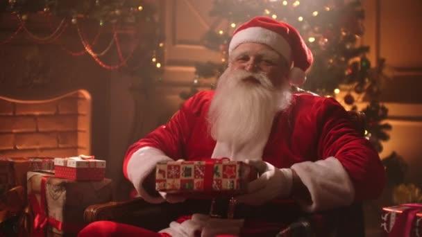 V magické atmosféře na Štědrý den, Santa podá dárek fotoaparátu s úsměvem.