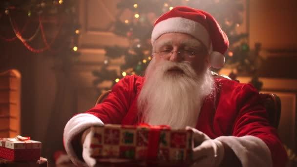 Starší muž s bílými vousy a kostýmem Santa Clause Ruce, dárek do kamery a usměje se
