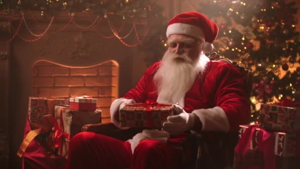 Mosolygó Mikulás ajándékokat ül egy székben