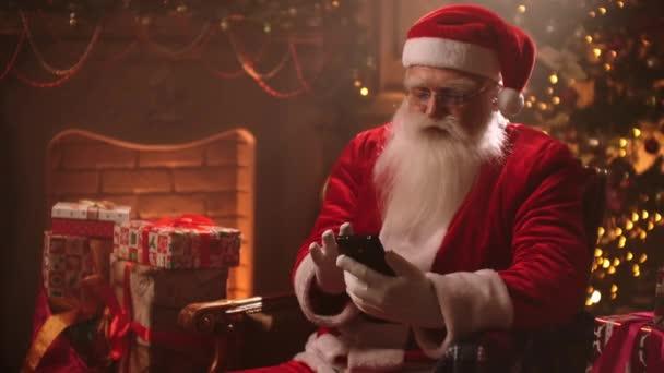 Moderní Santa Claus sedí na židli na pozadí vánočního stromečku pomocí smartphonu a chatuje a čte vzkazy od dětí.