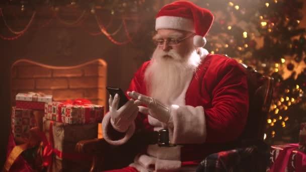 Santa Claus sedí v křesle na pozadí vánočního stromečku pomocí smartphonu a chatuje na internetu a čte vzkazy od dětí.