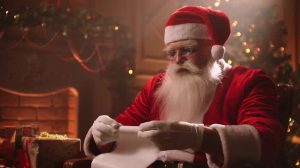 Santa Claus sroluje pergamenový svitek v kouzelném světle na pozadí vánočního stromku.