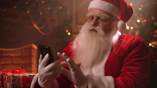 Santa Claus používá chytrý telefon a chatuje se svými asistenty a monitoruje situaci ve světě
