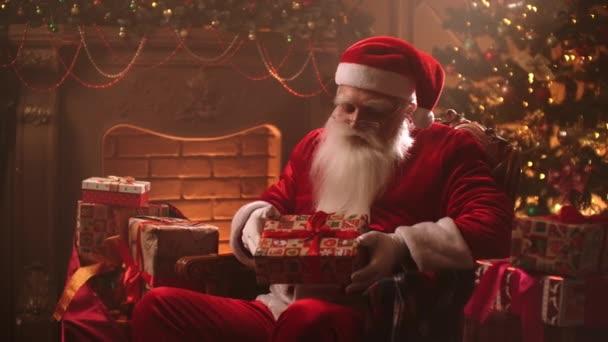 Santa Claus sedí a usmívá se dívá do kamery v magické atmosféře mezi dárky a vánoční stromeček