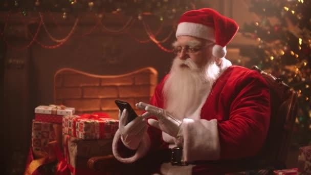 Mikulás ül egy széken a háttérben egy karácsonyfa segítségével egy okostelefon és megtekinti az online Bank számlák.