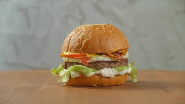Jeden hamburger na prkně a hranolky jsou rozházené. Detailní záběr lahodného čerstvého domácího burgeru se salátem, sýrem, cibulí a rajčaty na rustikálním dřevěném prkně na tmavém pozadí.