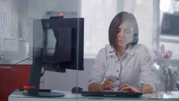 A woman doctor in a white coat looks at the monitor screen sitting in a bright office behind a glass wall. Modern clinic