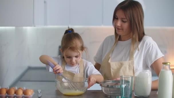 Holka ze školky pomáhá mámě v domácnosti s vařením. Milující matka učí dceru vařit podle rodinných recepty