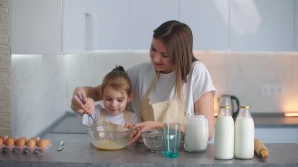 Kavkazská matka a dcera se baví při vydělávání těsta na kuchyni. Šťastná rodina v kuchyni. Malá dcerka připravuje těsto, pečou sušenky.