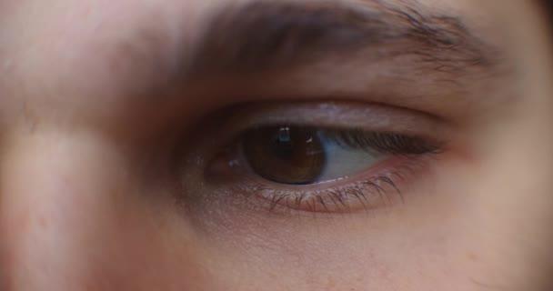 Augen eines ernsthaften kaukasischen Mannes, der seinen Tablet-Computer benutzt. Bildschirm reflektiert in den Augen, Gerätebeleuchtung leuchtet.