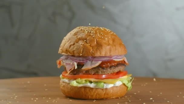 Bílá sezamová semínka pomalu padají do housky. Bun se sezamem na hamburger.