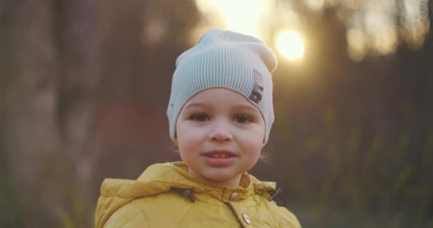Close-up portrait of a small smiling boy with large eyelashes in a cap and yellow jacket looking directly at the camera. Caucasian boy 2 years old