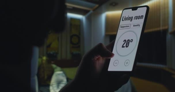 Ovládání teploty v domácnosti pomocí chytrého ovládání domu pomocí mobilního telefonu. Ruka drží smartphone s aplikací v obývacím pokoji pro ovládání bezpečnostních systémů