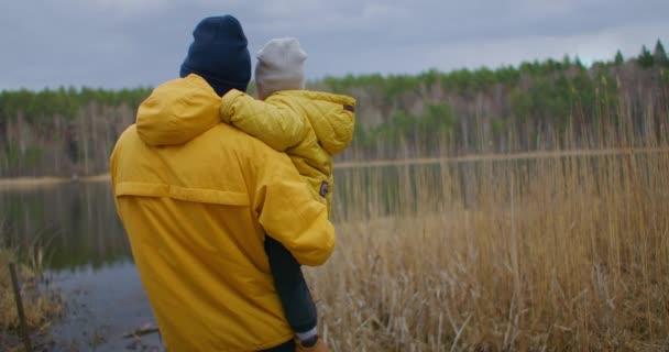 Otec drží svého syna v náručí a dívá se společně na jezero. Blízká spřízněnost otce a dítěte. Otcovství a životní styl v autentickém přírodním prostředí.