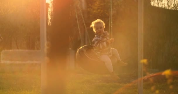 Little boy having fun on chain swing. Child on playground. swing Kids play outdoor. Smiling boy swinging on a rope at a playground.