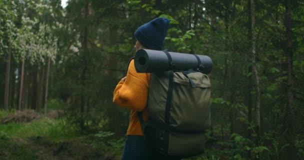 Közelkép vissza a nő hátizsák séta az őszi erdő természet táj utazás időjárás fa kültéri erdők lassított felvétel.