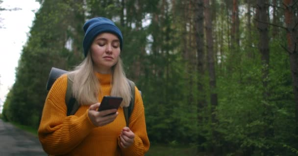 A female traveler holding a smartphone in a yellow sweater with a backpack is walking along a path in the forest looking at beautiful views. Take photos use the app and the Internet in the forest.