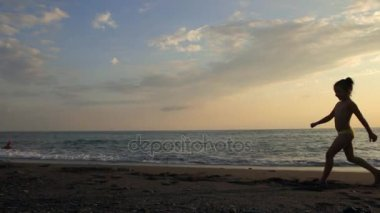 Little girl doing cartwheel on the beach on the beautiful sunset. Silhouette
