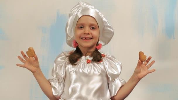 Dívka kuchař bez zub drží dvě sušenky ve tvaru srdce přes oči a usmál se