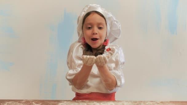Dívka kuchař bez zubů fouká do hrst mouky. Při pohledu na fotoaparát a smích.