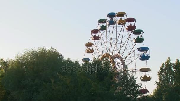 Riesenrad gegen den Himmel über den Bäumen am Abend.