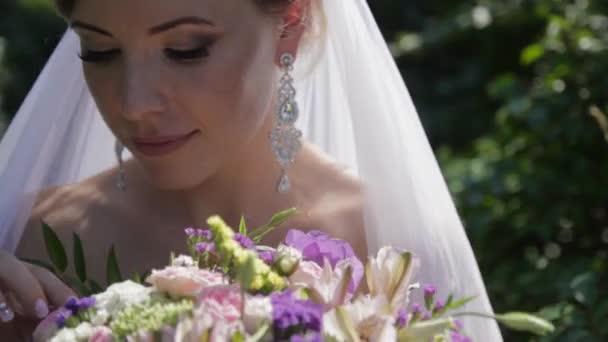 Mladá krásná nevěsta drží kytici květin. Portrét okouzlující dívka