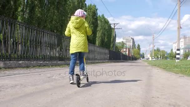 Malá holčička v zelené bundě a džíny jezdecké skútr na chodníku. Střelba Steadicam. Zpomalený pohyb.