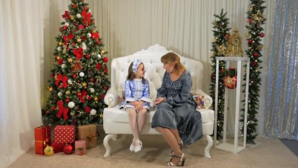 Mutter und Tochter geben sich gegenseitig Geschenke auf Neujahr Hintergrund der Weihnachtsbaum.
