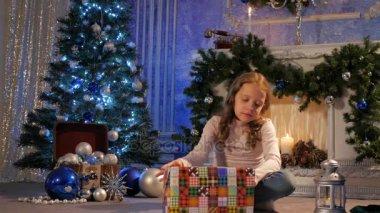 A little girl opens a Christmas gift.