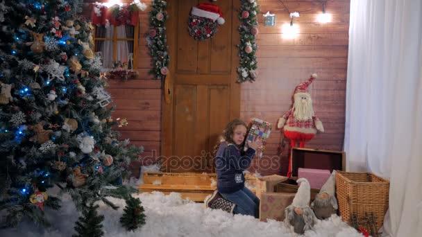 Malá holčička otevře vánoční dárek