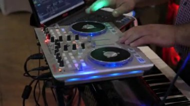 A professional DJ working in a club at a party winds and mixes music.
